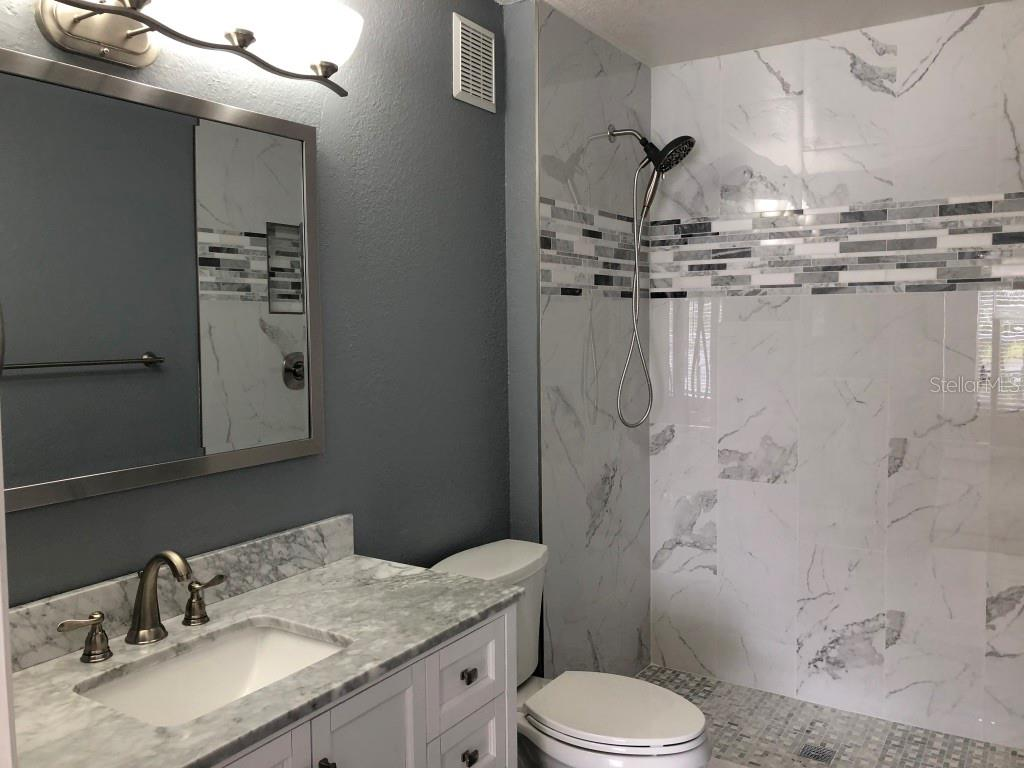 Master Bathroom with new cabinet with marble counter top and walk-in shower - Condo for sale at 8923 Manor Loop #106, Lakewood Ranch, FL 34202 - MLS Number is A4434002