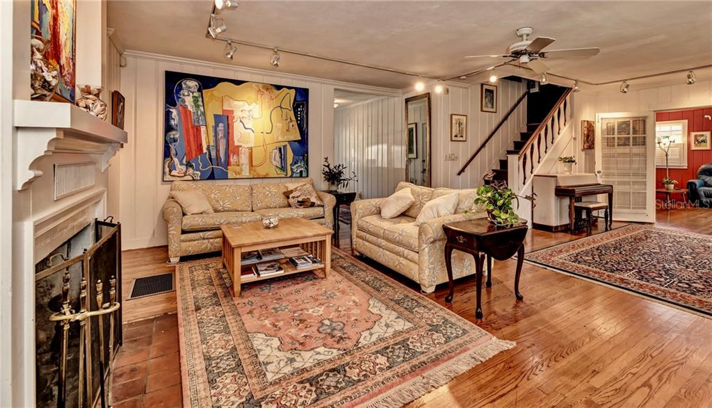A wide open yet cozy living room with the hallway from the entrance of the home, a beautiful staircase, a 1930s Art Deco (aka Style Moderne) Wurlitzer piano, and the entrance to a second, private seating/tv area,