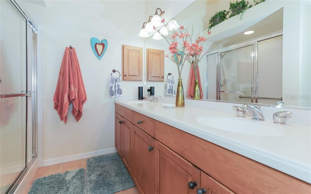 Master bathroom with dual sinks, corian counters and large vanity for abundant storage. - Condo for sale at 200 San Lino Cir #233, Venice, FL 34292 - MLS Number is A4440138