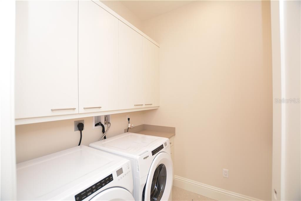 Spacious laundry room with washer, dryer, utility sink and above storage. - Condo for sale at 609 Golden Gate Pt #202, Sarasota, FL 34236 - MLS Number is A4441802