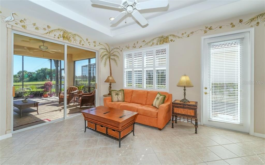 Tiled living room with large window with plantation shutters and sliding door access to oversized lanai. - Single Family Home for sale at 114 Padova Way #52, North Venice, FL 34275 - MLS Number is A4442496