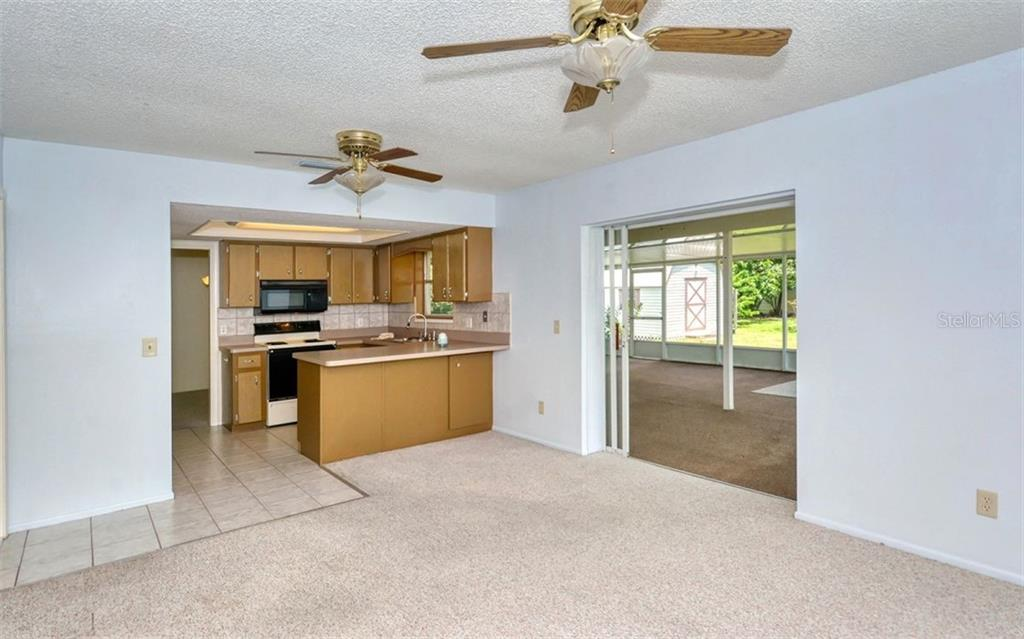 The family room opens up the the large under cover lanai with pocketing sliding glass doors! - Single Family Home for sale at 3286 Jamestown St, Port Charlotte, FL 33952 - MLS Number is A4444310
