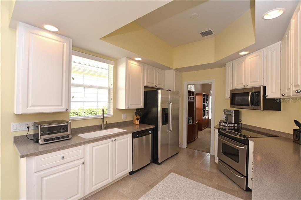 Kitchen offers stainless appliances, breakfast bar & nearby sliders to the lanai. - Single Family Home for sale at 5799 Benevento Dr, Sarasota, FL 34238 - MLS Number is A4450677