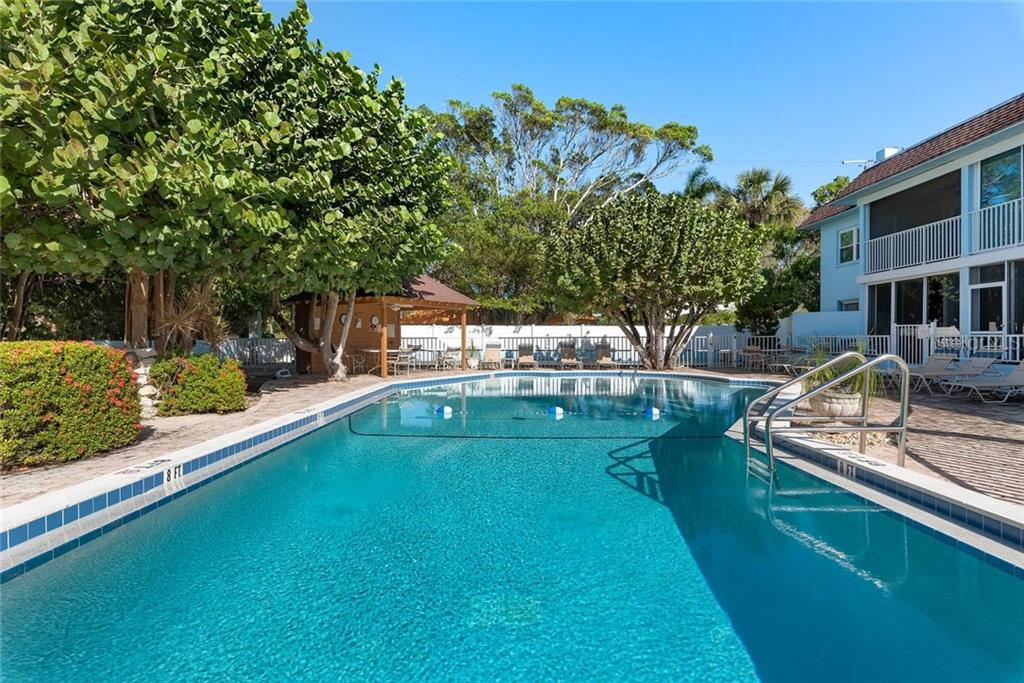 The pool area has a grill located under the mature trees and a shuffleboard court on the other side - Condo for sale at 4307 Gulf Dr #209, Holmes Beach, FL 34217 - MLS Number is A4452656