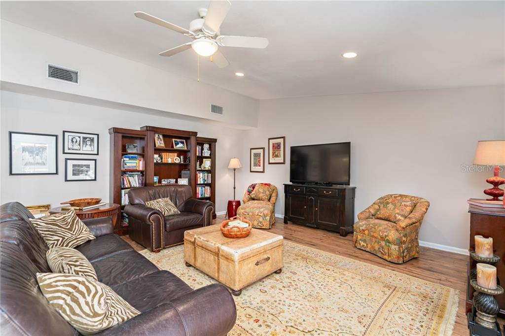 Family room with wood floors, high ceilings and new paint. - Single Family Home for sale at 4557 Camino Real, Sarasota, FL 34231 - MLS Number is A4457740
