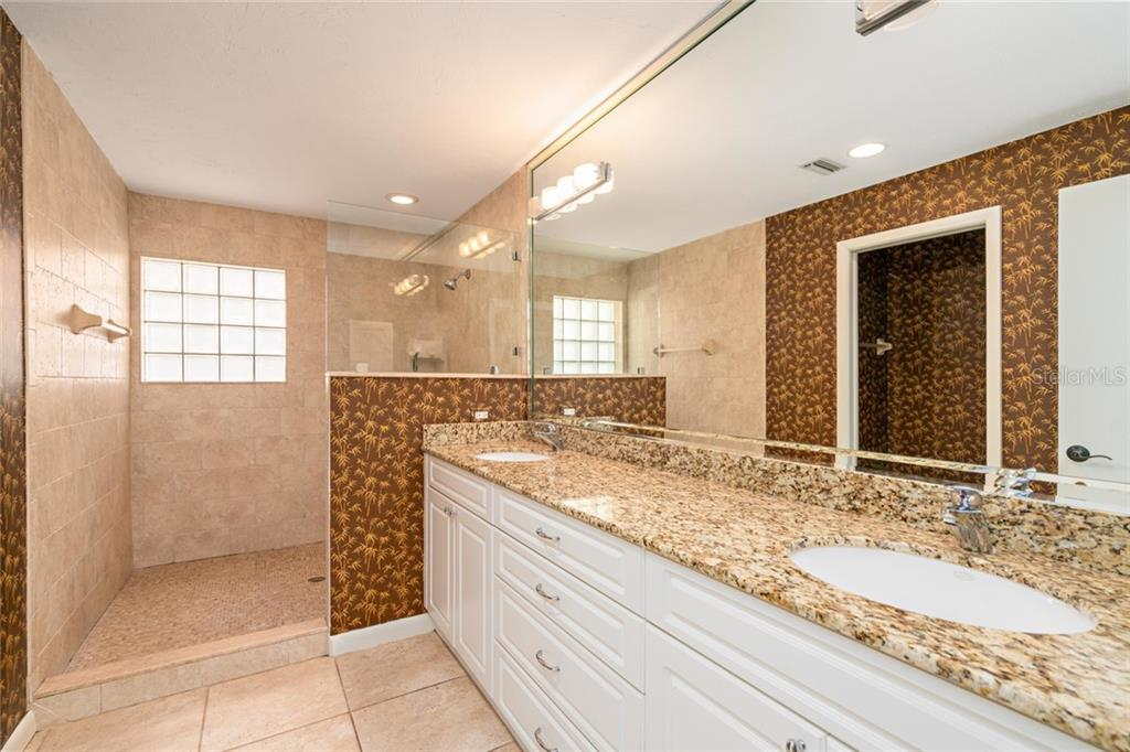 En suite bathroom with extra large walk in shower and huge vanity with double sinks. - Single Family Home for sale at 4557 Camino Real, Sarasota, FL 34231 - MLS Number is A4457740
