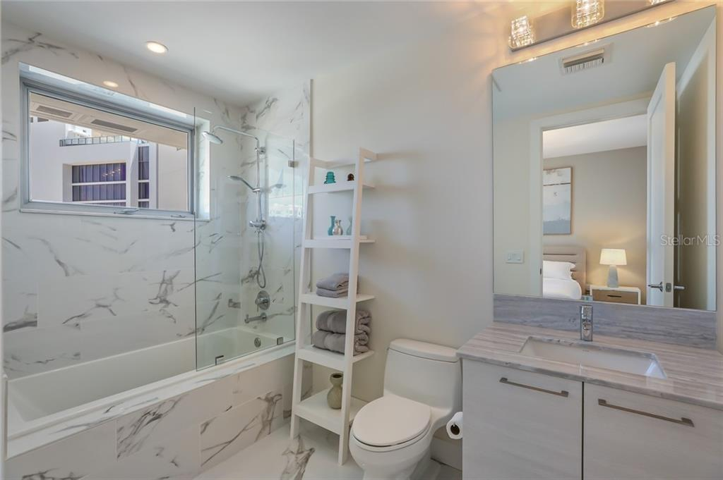 The en suite guest bath is chic, chic, chic! - Condo for sale at 1155 N Gulfstream Ave #1404, Sarasota, FL 34236 - MLS Number is A4467921
