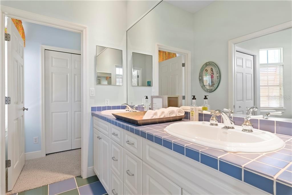 Jack and Jill bathroom for main level bedrooms with dual vanities, walk in shower and claw foot tub - Single Family Home for sale at 97 52nd St, Holmes Beach, FL 34217 - MLS Number is A4468151