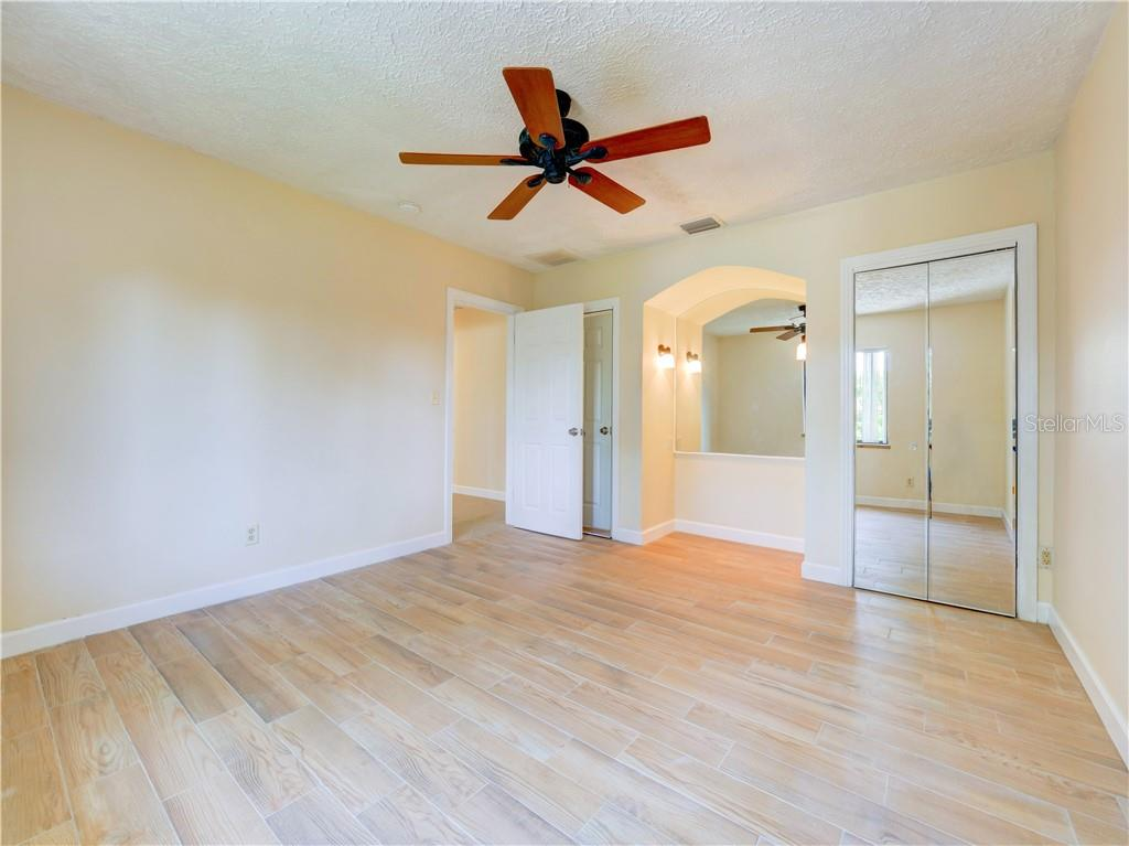 Third bedroom features a ceiling fan, two closets with full length mirrored doors and a perfect nook for a dressing table or desk. - Single Family Home for sale at 2408 Riverside Dr E, Bradenton, FL 34208 - MLS Number is A4480609