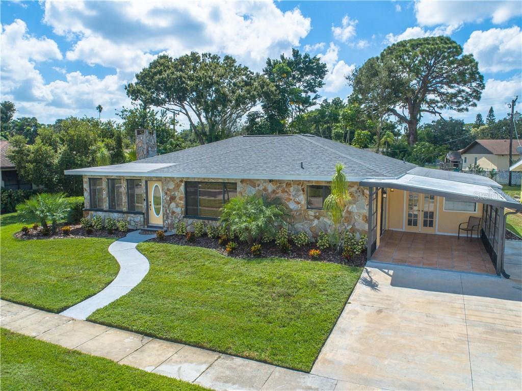 Front elevated view of home.  The tiled carport would also make a great sitting area from which you could enjoy the expansive river views and breeze. - Single Family Home for sale at 2408 Riverside Dr E, Bradenton, FL 34208 - MLS Number is A4480609