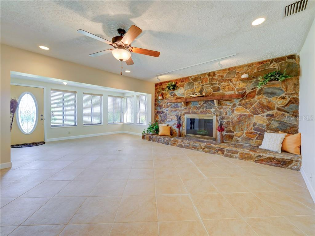 Entry and living room with custom stone fireplace. - Single Family Home for sale at 2408 Riverside Dr E, Bradenton, FL 34208 - MLS Number is A4480609