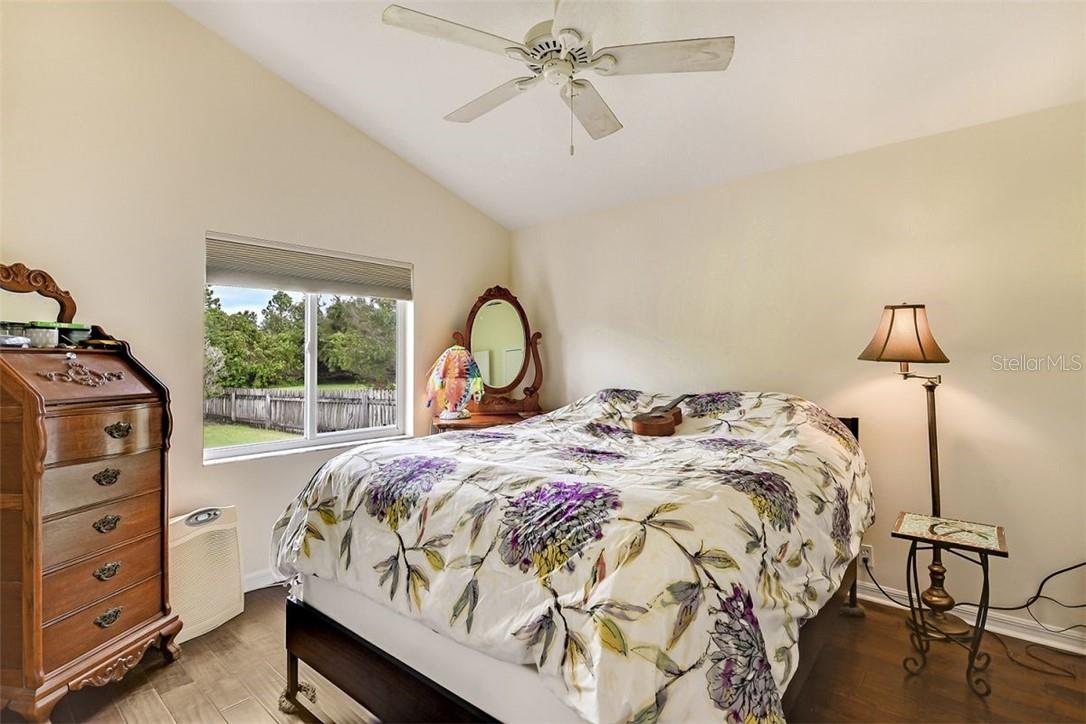Guest bedroom with engineered wood floors and views of backyard - Single Family Home for sale at 7832 Panther Ridge Trl, Bradenton, FL 34202 - MLS Number is A4483837