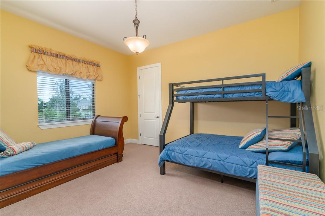 The second of the secondary bedrooms is set up with bunk beds for the family's grandchildren and features a walk-in closet. - Single Family Home for sale at 11720 Rive Isle Run, Parrish, FL 34219 - MLS Number is A4486302