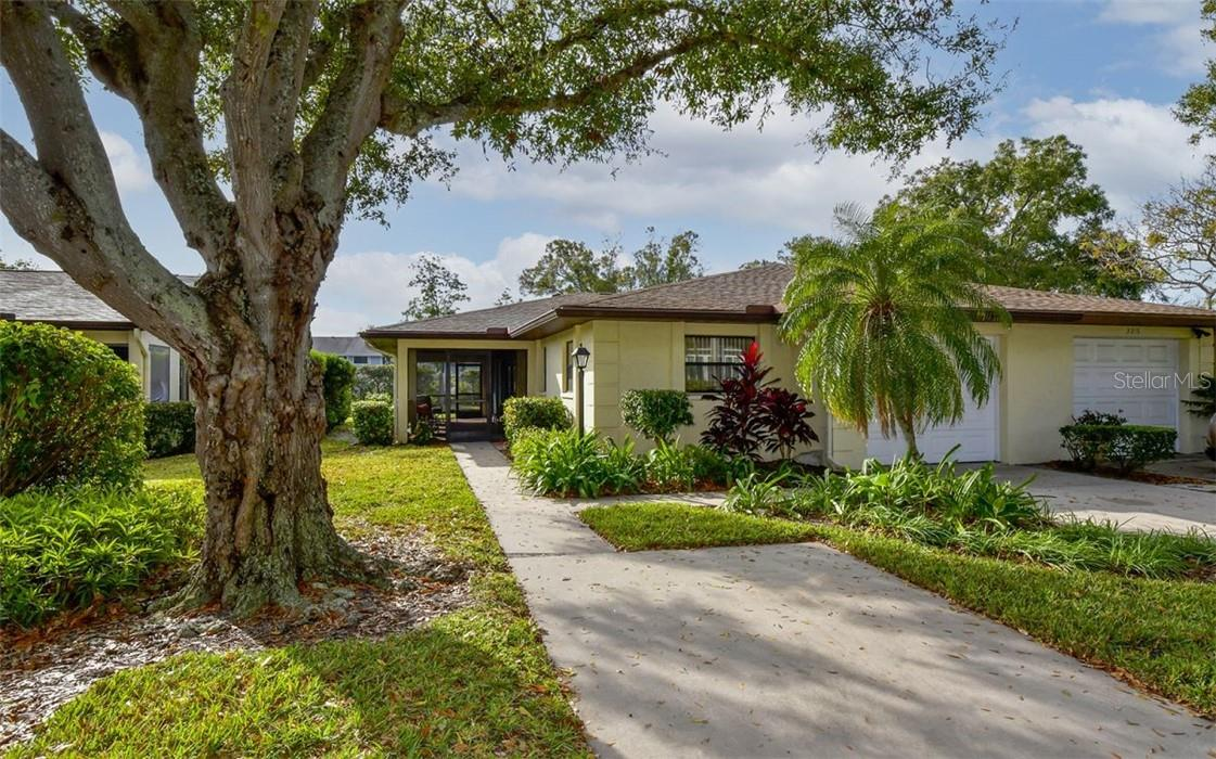 Framed by a beautiful shade tree, extra parking pad & sidewalk to front door entry. - Villa for sale at 3314 Vivienda Blvd, Bradenton, FL 34207 - MLS Number is A4488348