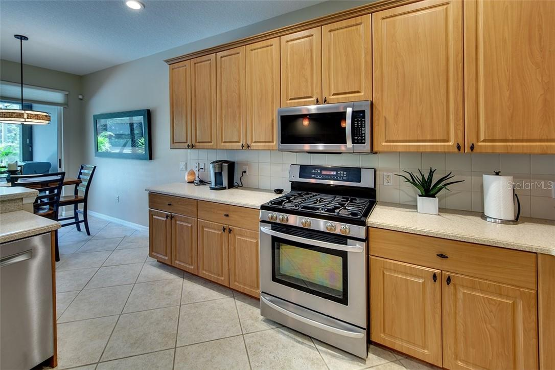 Gourmet Kitchen Features Stainless Steal Appliances and Tile Backsplash - Single Family Home for sale at 7739 Us Open Loop, Lakewood Ranch, FL 34202 - MLS Number is A4494156