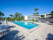 community clubhouse swimming pool with paver brick sun deck - Condo for sale at 19 Whispering Sands Dr #205, Sarasota, FL 34242 - MLS Number is A4189914