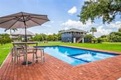 Pool with carriage house beyond. - Single Family Home for sale at 590 Bayshore Dr, Terra Ceia, FL 34250 - MLS Number is A4437024