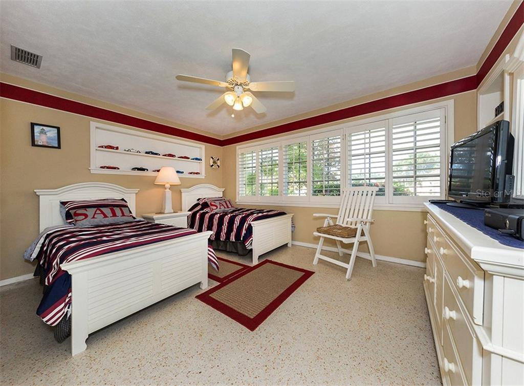 Guest bedroom with terrazzo floors, built in shelves, and plantation shutters. - Single Family Home for sale at 620 Valencia Rd, Venice, FL 34285 - MLS Number is N6100912