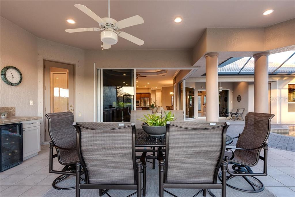 Cabana with outdoor kitchen and view of the zero return sliding glass doors to leisure room, and to left door to pool bath - Single Family Home for sale at 821 Adonis Pl, Venice, FL 34292 - MLS Number is N6104303