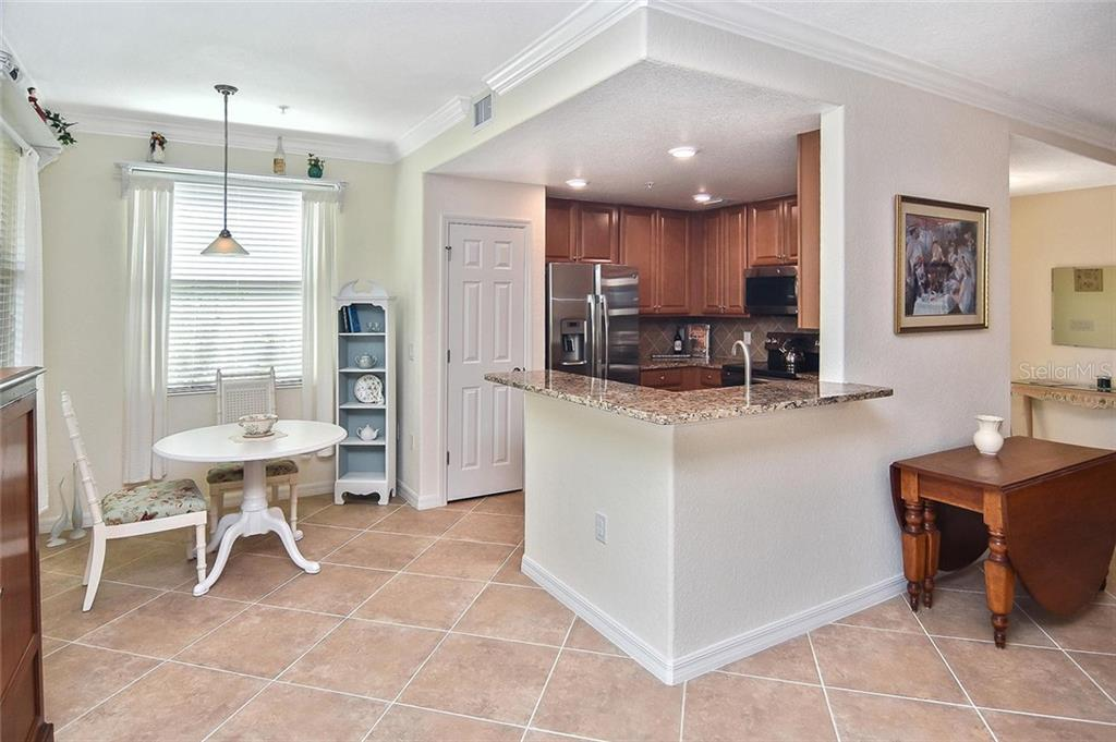 Kitchen with pantry, granite counters, stainless steel appliances, wood cabinets, tile backsplash and recessed lighting. - Condo for sale at 20111 Ragazza Cir #102, Venice, FL 34293 - MLS Number is N6105517