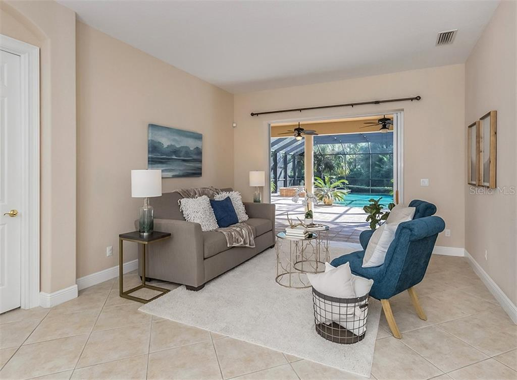 Living room with slider to lanai and pool - Single Family Home for sale at 106 Vicenza Way, North Venice, FL 34275 - MLS Number is N6106168