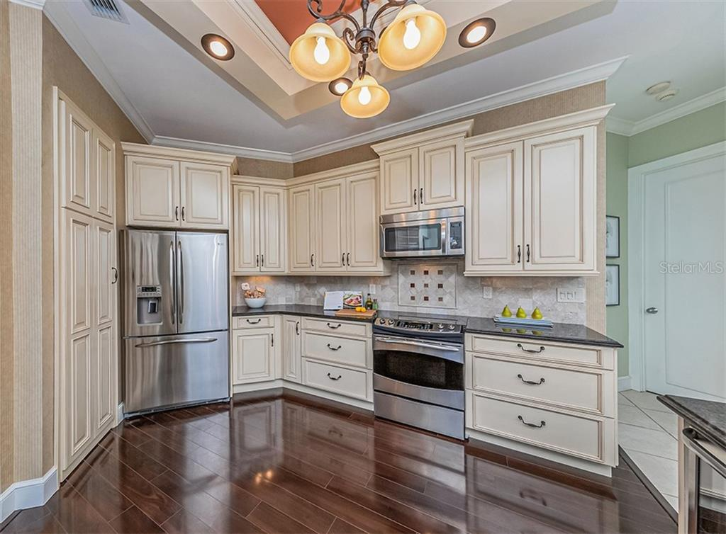 Handsome wood floors compliment the glazed cabinetry and stainless appliances - Single Family Home for sale at 727 Eagle Point Dr, Venice, FL 34285 - MLS Number is N6110087