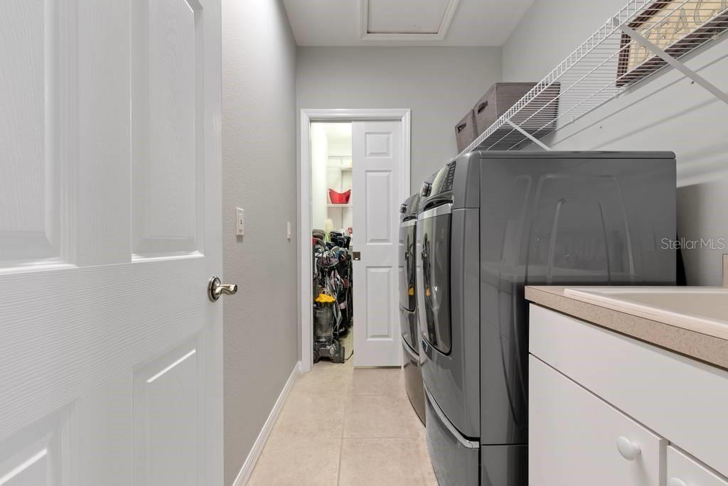Laundry room with sink, stacked washer/dryer and additional storage/pantry - Single Family Home for sale at 601 Cockatoo Cir, Venice, FL 34285 - MLS Number is N6111658