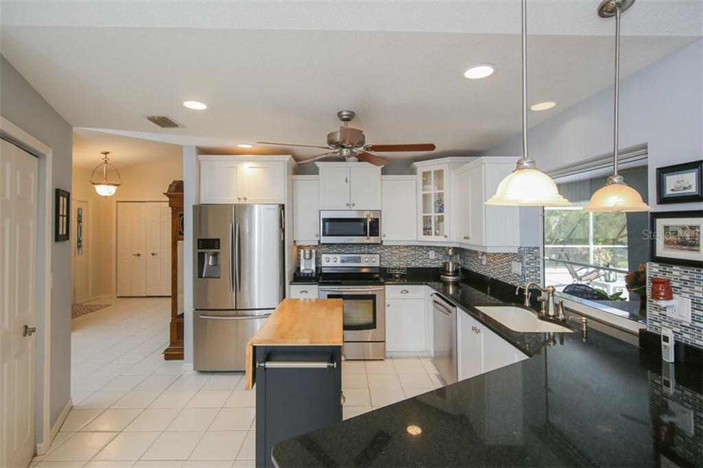 Gourmet Kitchen White Thermofoil Cabinets, Granite Counters, Center Island  That Conveys, And Samsung