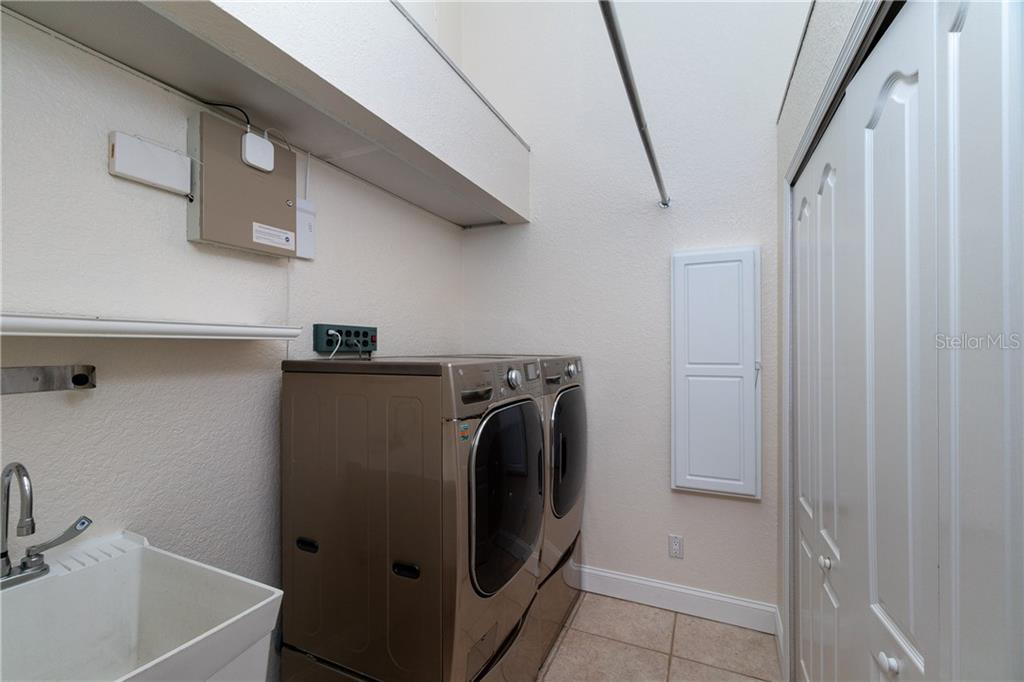 Nice size Laundry room off Kitchen with front loader washer & dryer, deep sink, built in ironing board and lots of closet space. Another added bonus to this room is access to an air conditioned attic that has flooring with carpet, drywall and paint. Size is approximately 10 x 6. - Single Family Home for sale at 1309 Casey Key Dr, Punta Gorda, FL 33950 - MLS Number is C7413790