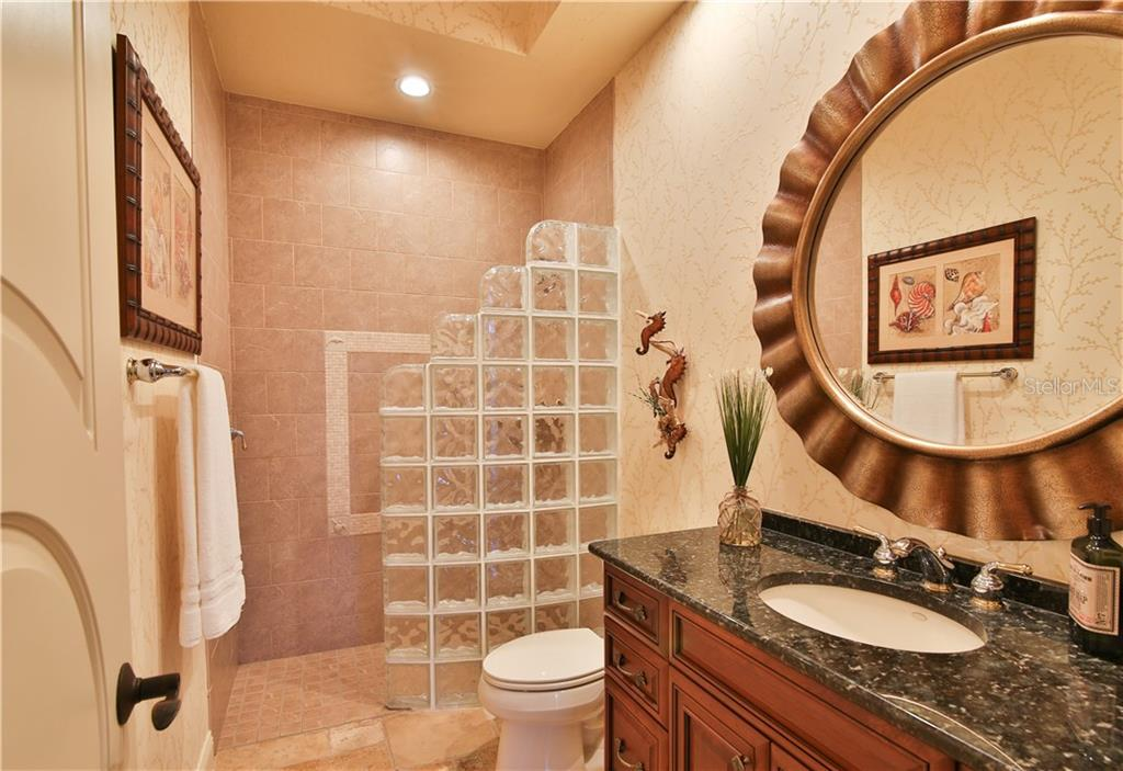 The pool bath, full bath with shower.  Notice the door - these solid core doors with oiled bronze hardware are found all throughout the home. - Single Family Home for sale at 8365 Catamaran Cir, Lakewood Ranch, FL 34202 - MLS Number is A4187448