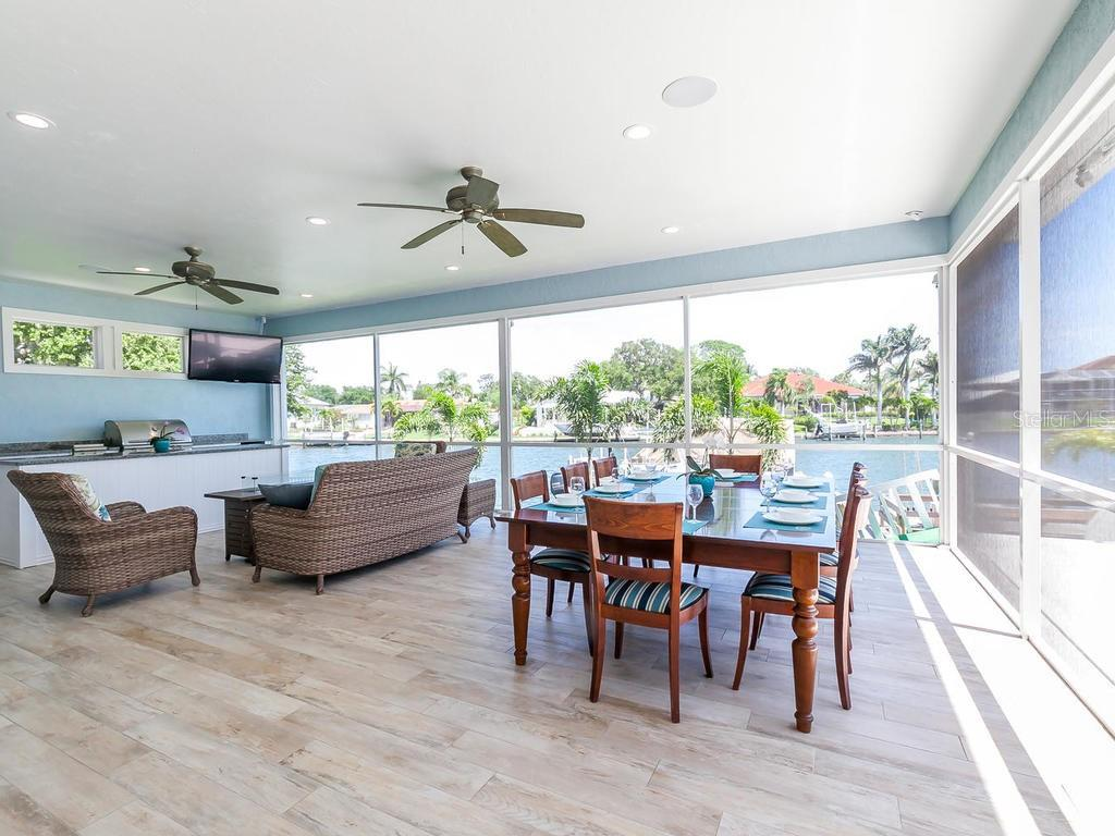 Downstairs outdoor screened entertaining area with island.  Built in grill and sink, refrigerator and beautiful water views - Single Family Home for sale at 7643 Cove Ter, Sarasota, FL 34231 - MLS Number is A4403215