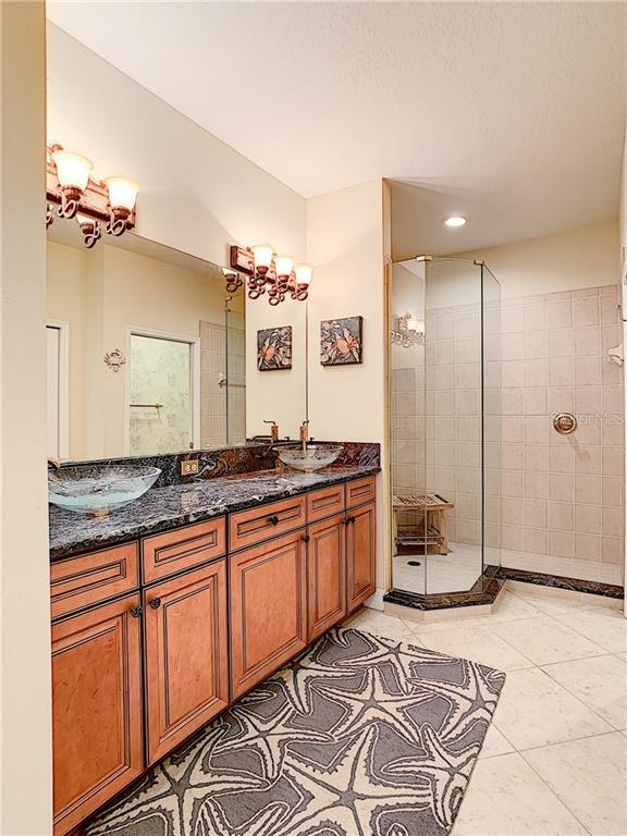 Luxurious master bath with vessel sinks and frameless glass shower. - Condo for sale at 9453 Discovery Ter #201c, Bradenton, FL 34212 - MLS Number is A4423314