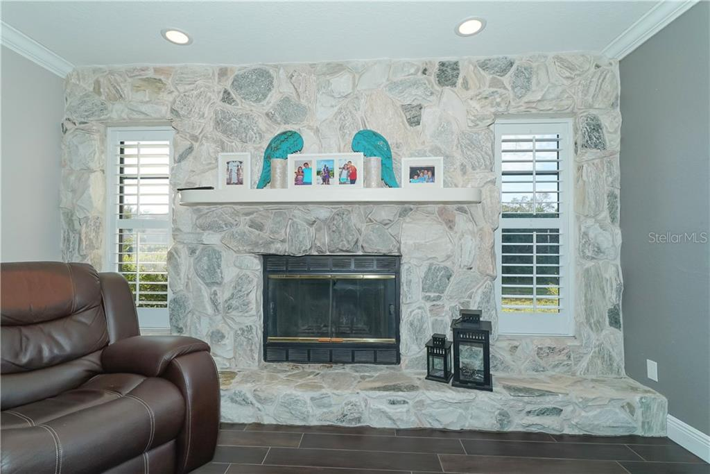 Stone fireplace and plantation shutters on the windows. - Single Family Home for sale at 8106 Timber Lake Ln, Sarasota, FL 34243 - MLS Number is A4423770