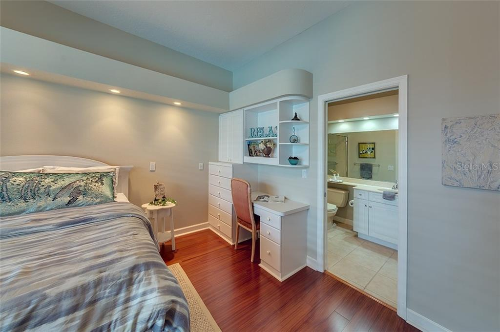 Cozy ensuite guest bedroom with built in cabinetry and built in desk. - Single Family Home for sale at 2972 Jeff Myers Cir, Sarasota, FL 34240 - MLS Number is A4424133
