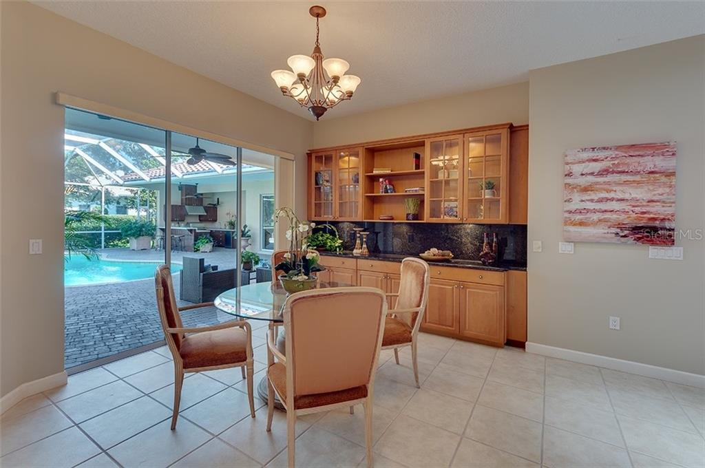 Kitchen eating area with sliders leading to the courtyard - plus loads of built-in cabinetry! - Single Family Home for sale at 2972 Jeff Myers Cir, Sarasota, FL 34240 - MLS Number is A4424133