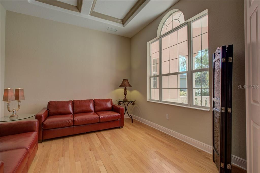 Den/Office with double-door entry, coffered ceiling, wood floors, and large window. - Single Family Home for sale at 15109 17th Ave E, Bradenton, FL 34212 - MLS Number is A4425963