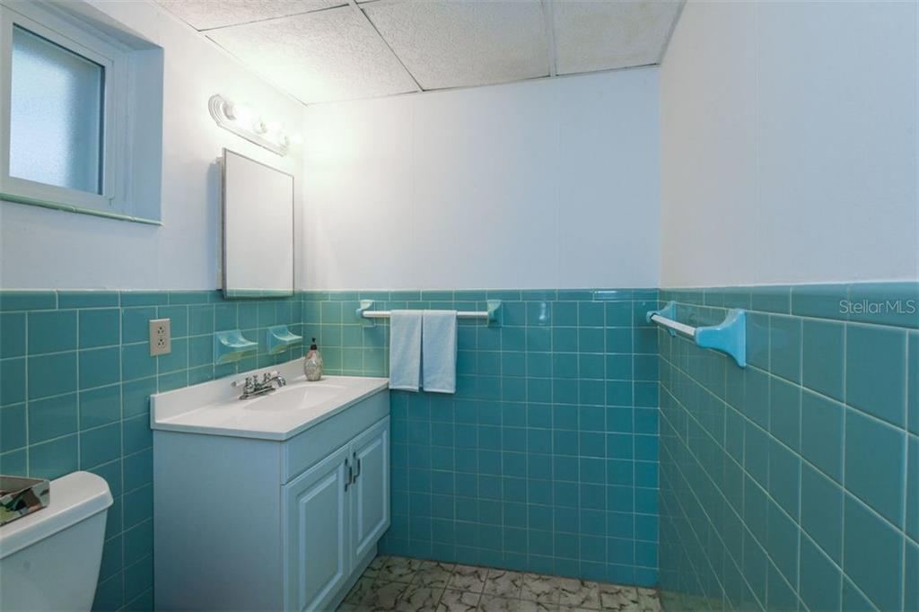 The downstairs powder room has been updated but still retains the original flooring and turquoise tile walls. - Single Family Home for sale at 7727 Westmoreland Dr, Sarasota, FL 34243 - MLS Number is A4430900