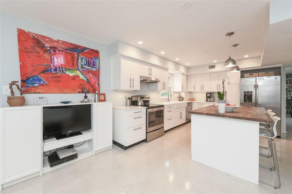 Sleek, remodeled kitchen features white quartz countertops and an abundance of upper cabinets. - Single Family Home for sale at 7727 Westmoreland Dr, Sarasota, FL 34243 - MLS Number is A4430900