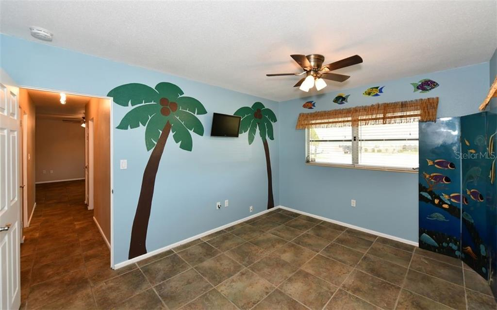 Bedroom 2 with a tropical theme. - Single Family Home for sale at 120 23rd Street Ct Ne, Bradenton, FL 34208 - MLS Number is A4438232